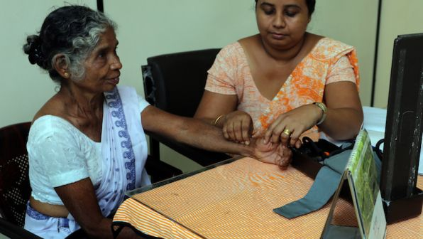 A doctor checks the pulse of an elderly female patient in Sri Lanka.