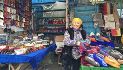 A woman sells hats and slippers at the bazaar.