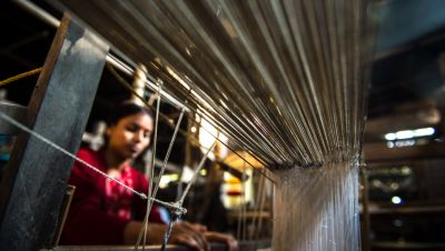An Indian woman weaving silk with a powerloom in Assam.