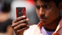 A young man takes a photo with his smartphone in Bangladesh.